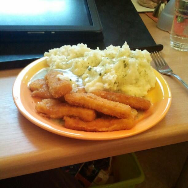 Stäbchen des Fisches mit Püree der Kartoffel.